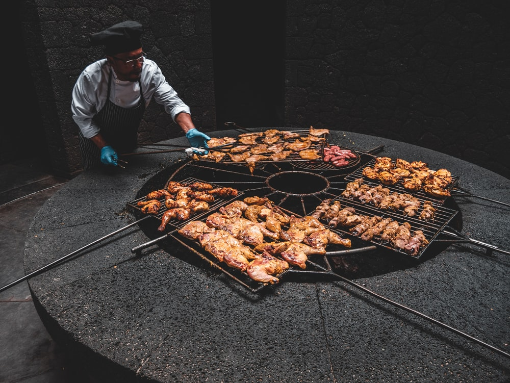 male chef standing while roasting chicken