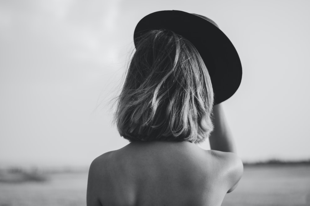 grayscale photography woman holding hat