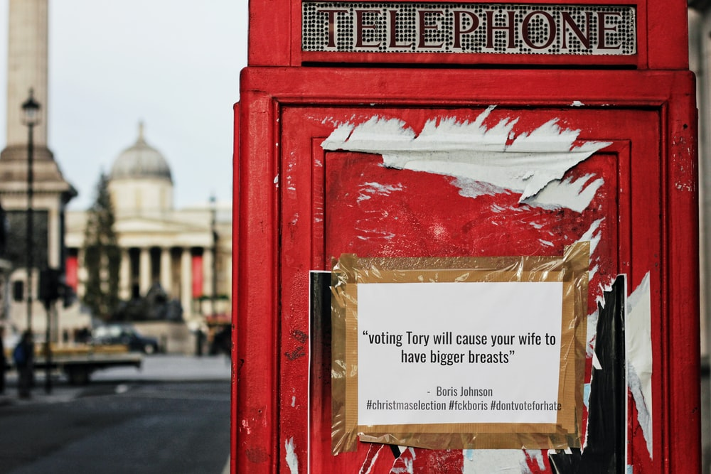 white printed poster displayed on a red telephone booth