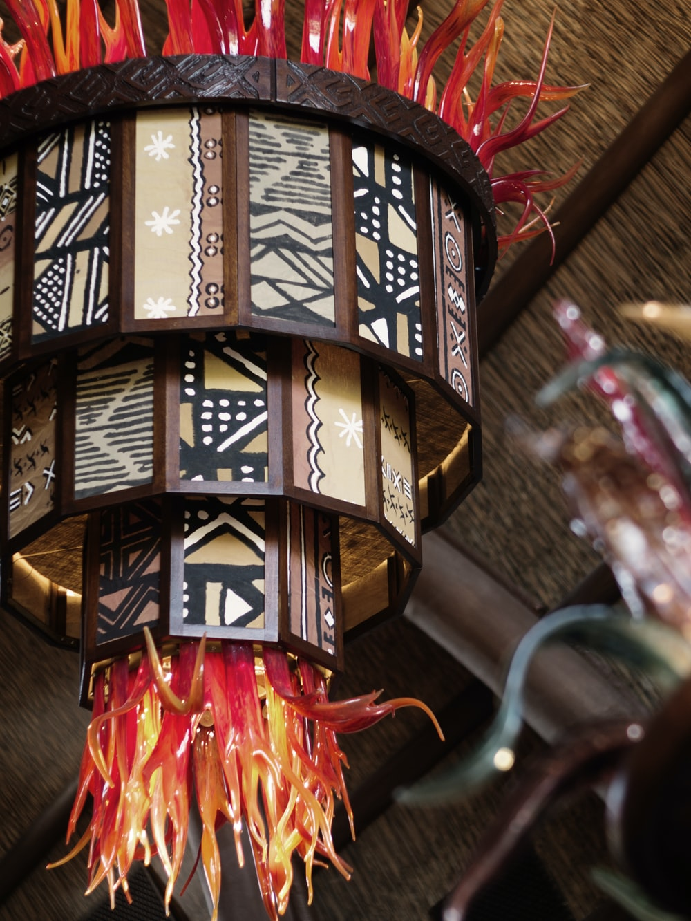 focus photography of brown tribal chandelier with orange fringe