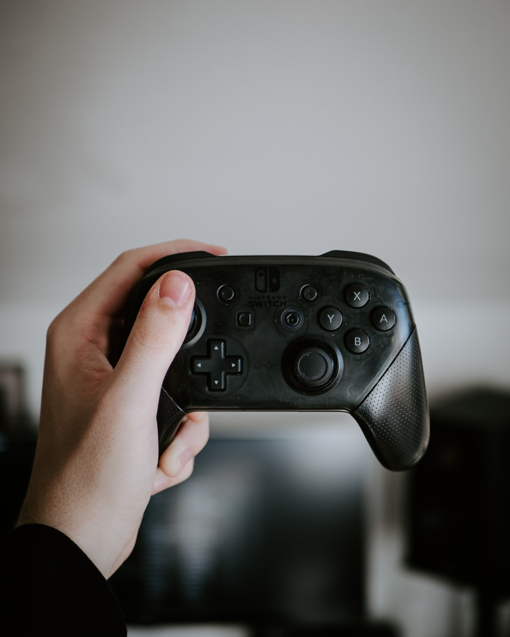 person holding black Nintendo Switch Joy-Con