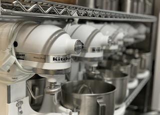 white KitchenAid stand mixers on gray shelf