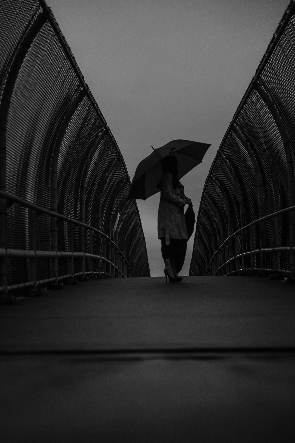 grayscale photography of woman using umbrella while standing on pathway