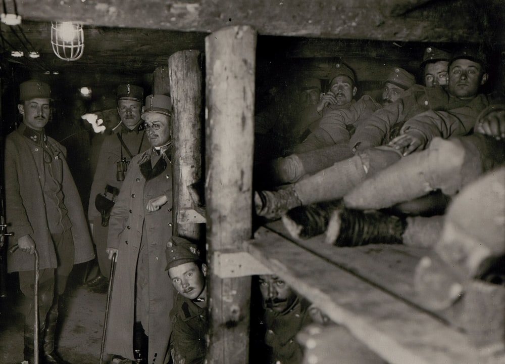 grayscale photography of soldier men inside cave