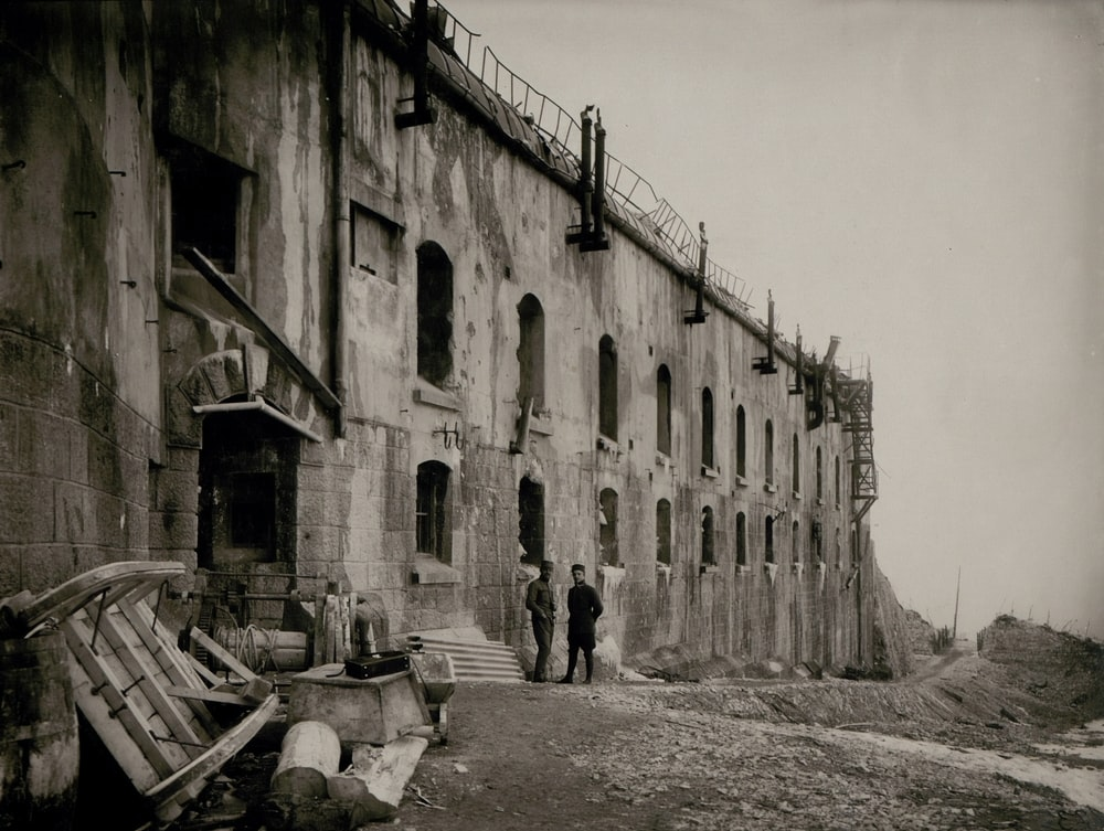 grayscale photography of two men standing outside a concrete building