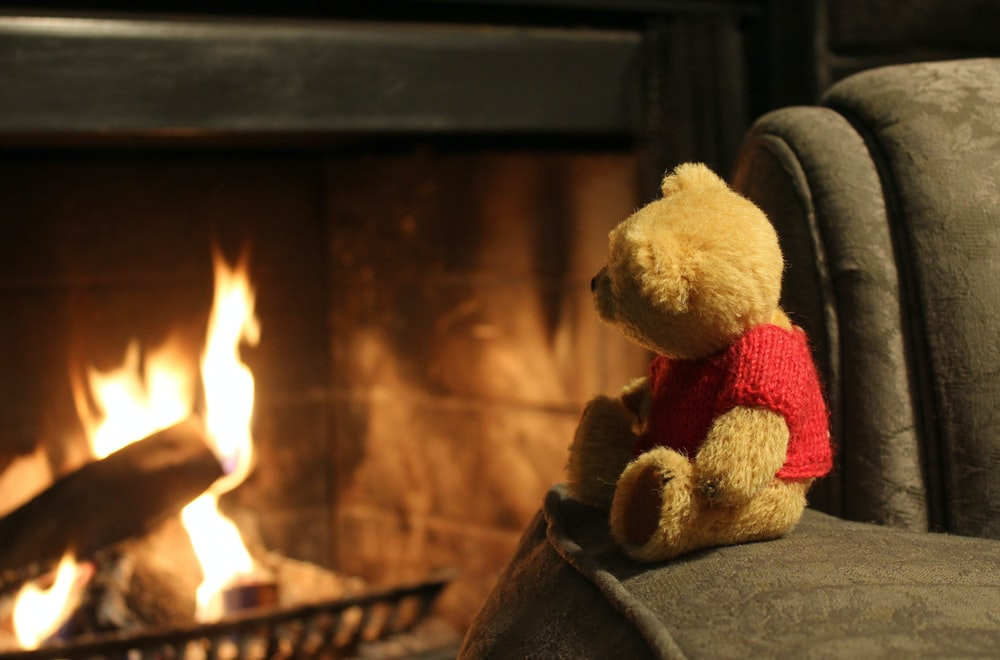 Winnie the Pooh plush toy placed on a sofa near a fireplace