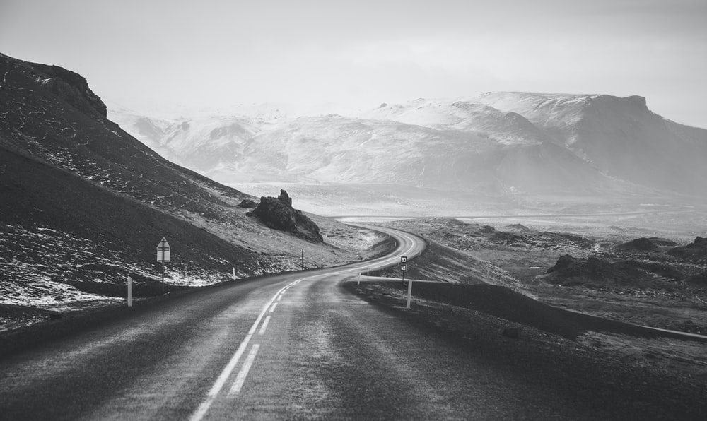 grayscale photography of road viewing mountain