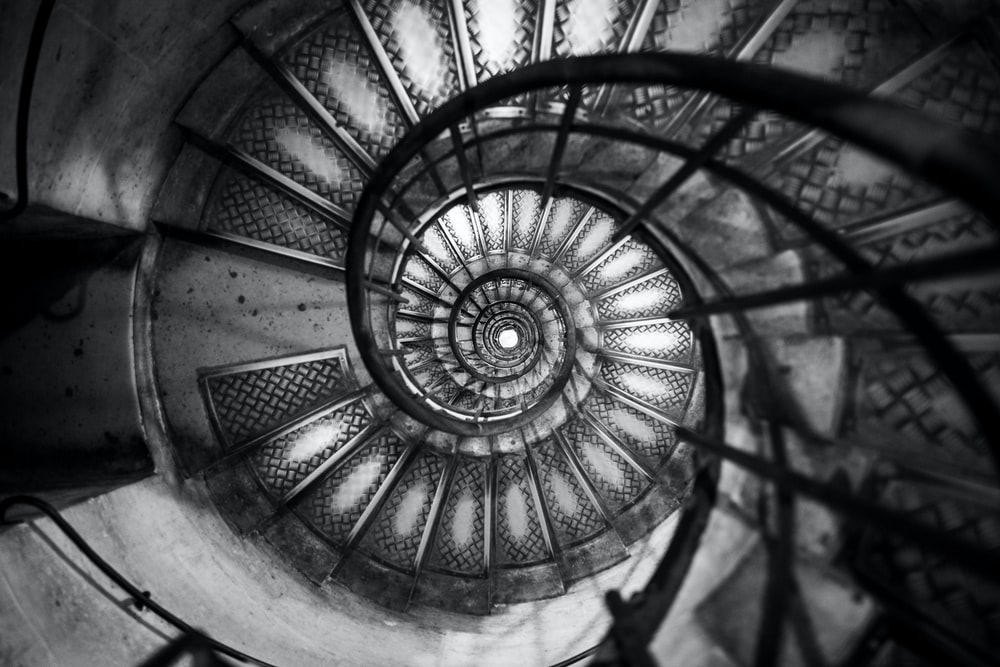 top view of spiral stairs in grayscale photo