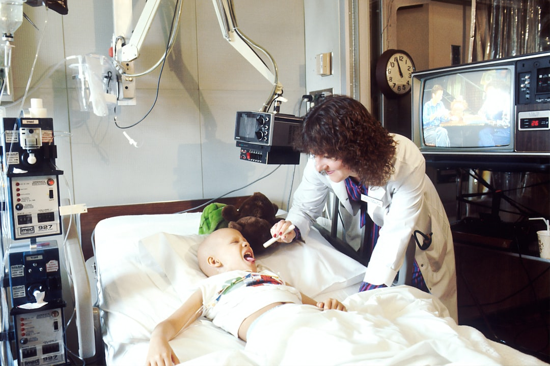 A doctor examines a pediatric patient who is receiving chemotherapy.