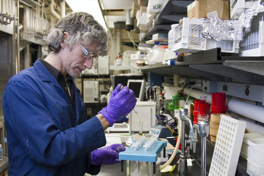 woman dropping a specimen on a test tube