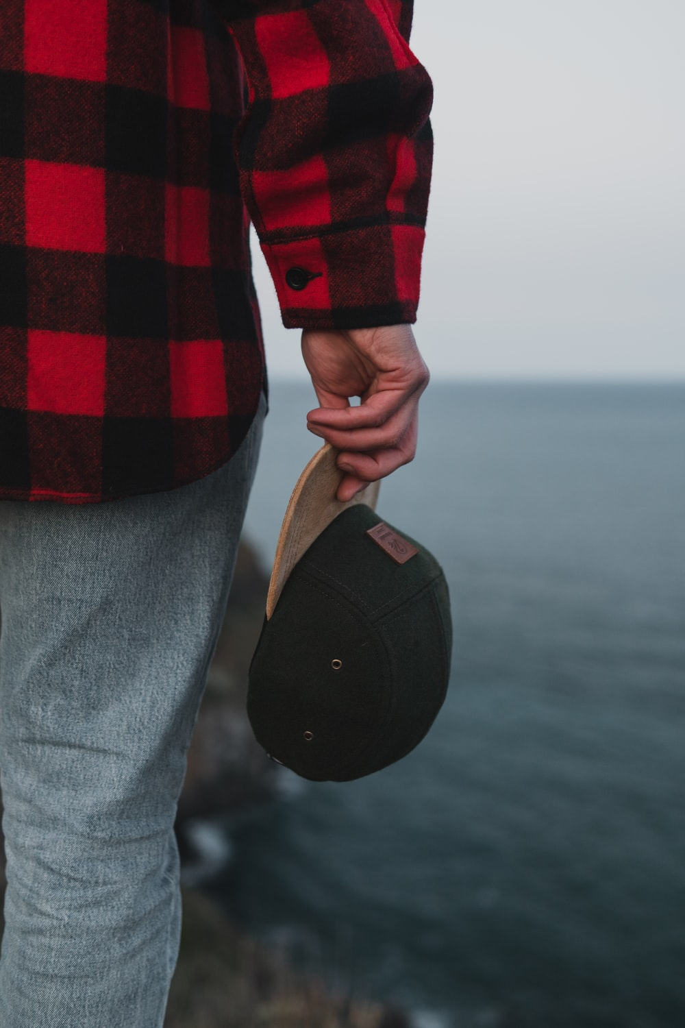 person wearing red and black long-sleeved shirt holding black and brown fitted cap while standing on cliff viewing body of water