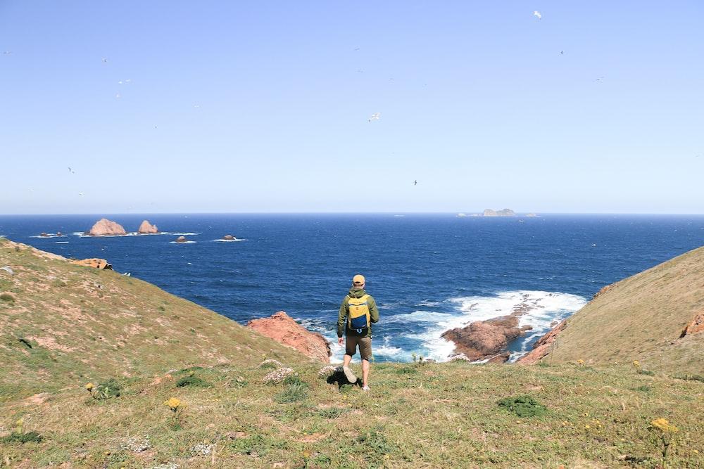 man on hill near sea