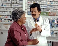 """Woman Consults with Pharmacist. An older African-American woman talks to a Hispanic male pharmacist as he explains her prescription. Photographer Rhoda Baer"""