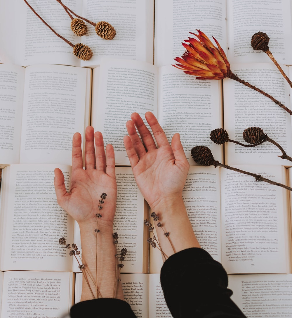 person holding out two hands beside flowers on open books