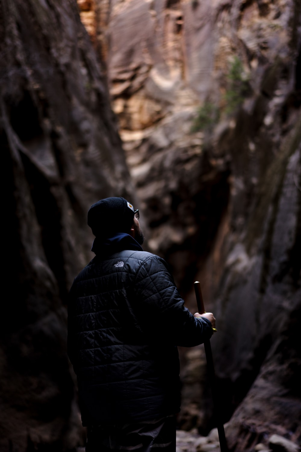 man wearing black jacket holding stick while standing near cave during daytime