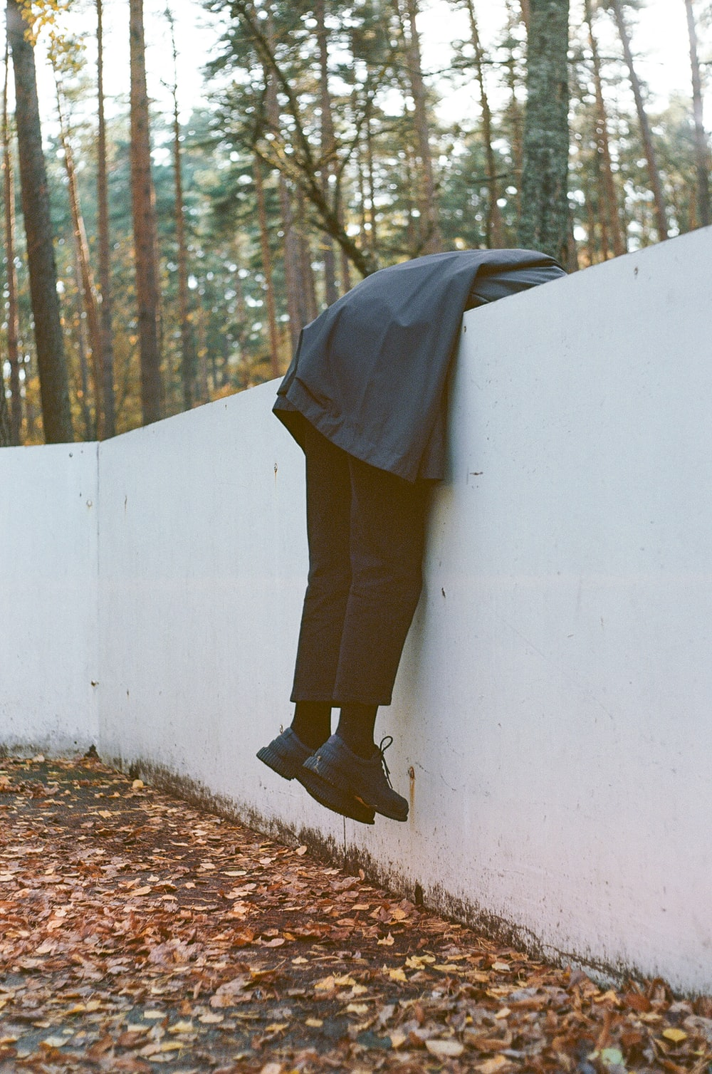 person leaning on white concrete fence