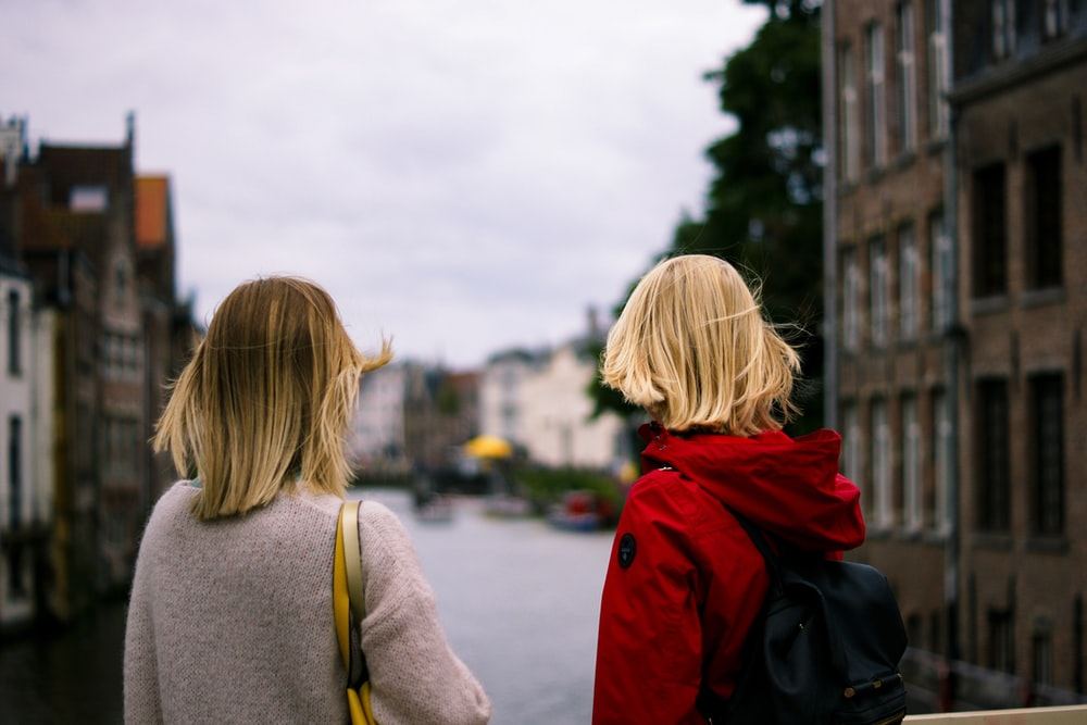 two women in gray sweater and red hooded jacket