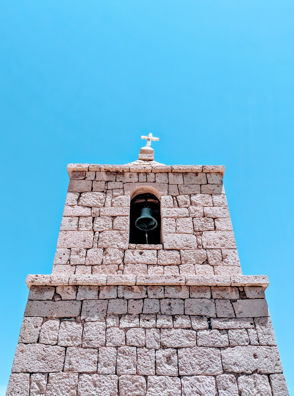 low-angle photography of a church bell under a calm blue sky