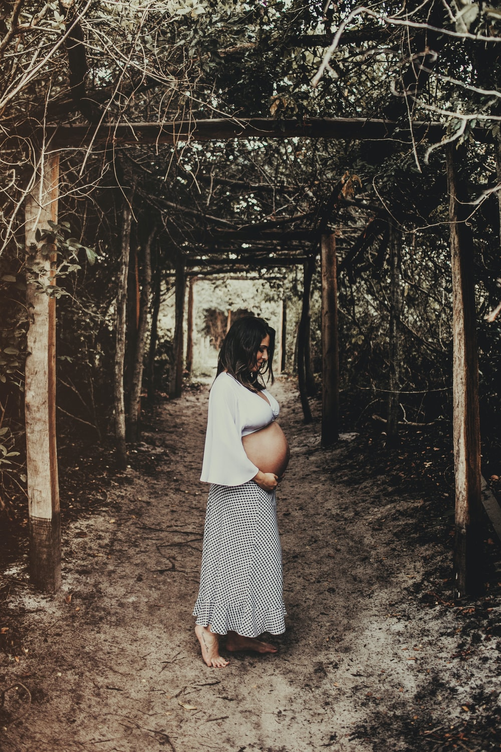 pregnant woman standing in tree tunnel