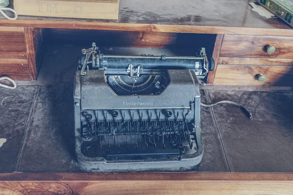 vintage gray typewriter on black and brown wooden desk