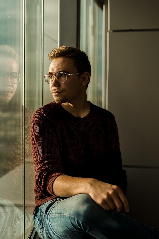 man sitting near glass wall