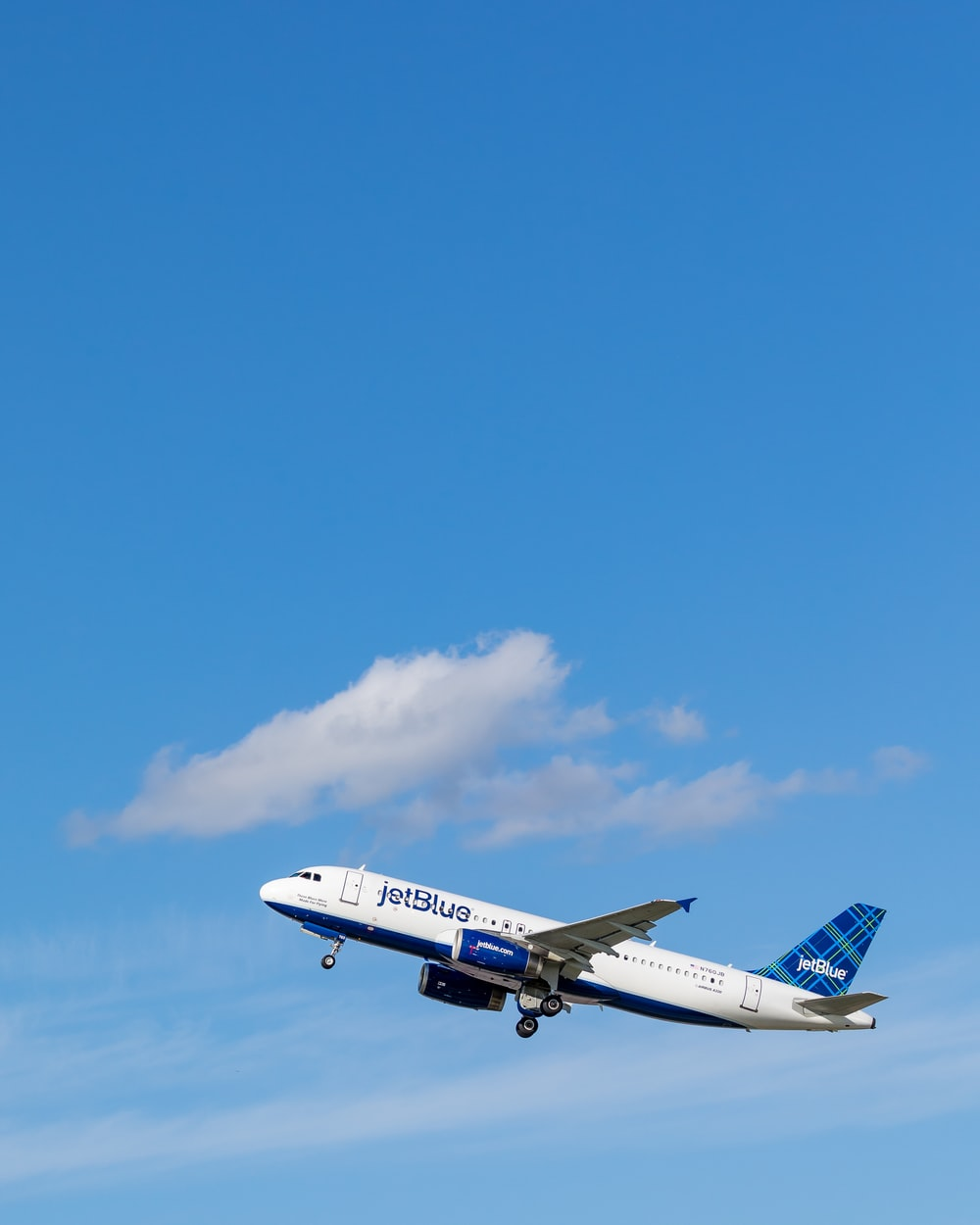 white and blue Jetblue airliner flying on sky