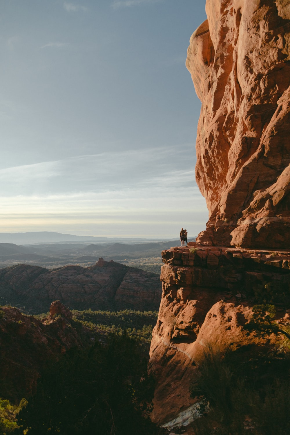 man and woman standing on mountain cliff during daytime