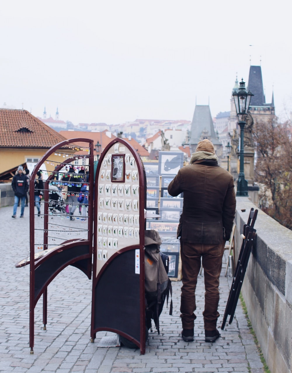 man standing beside brown wooden folding rack near fence