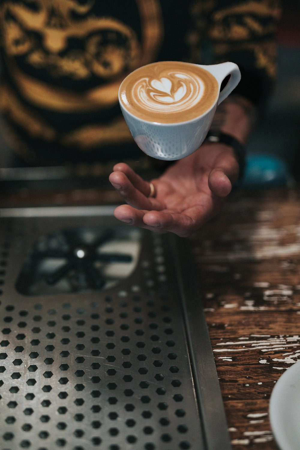 cup of cafe over person's hand