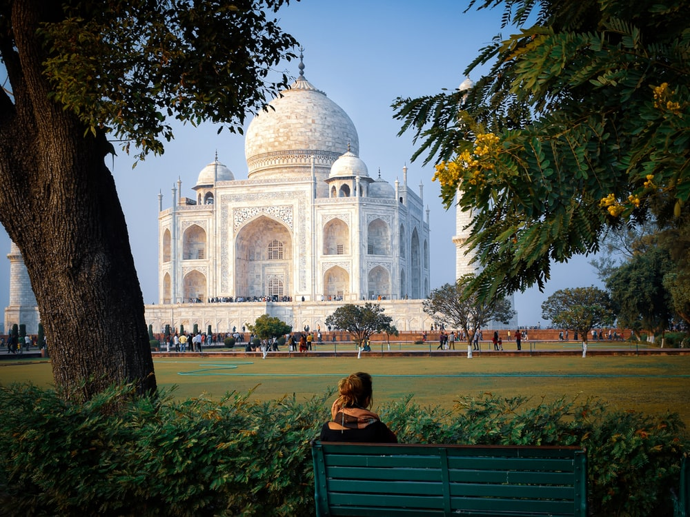 man sitting on bench near trees and people near Taj Mahal, India during day