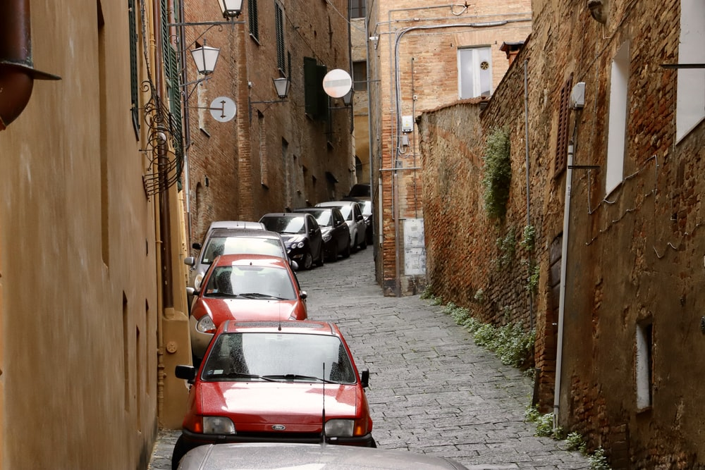 cars parked on alley beside walls