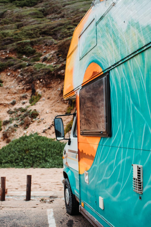 green and orange RV parked near mountain