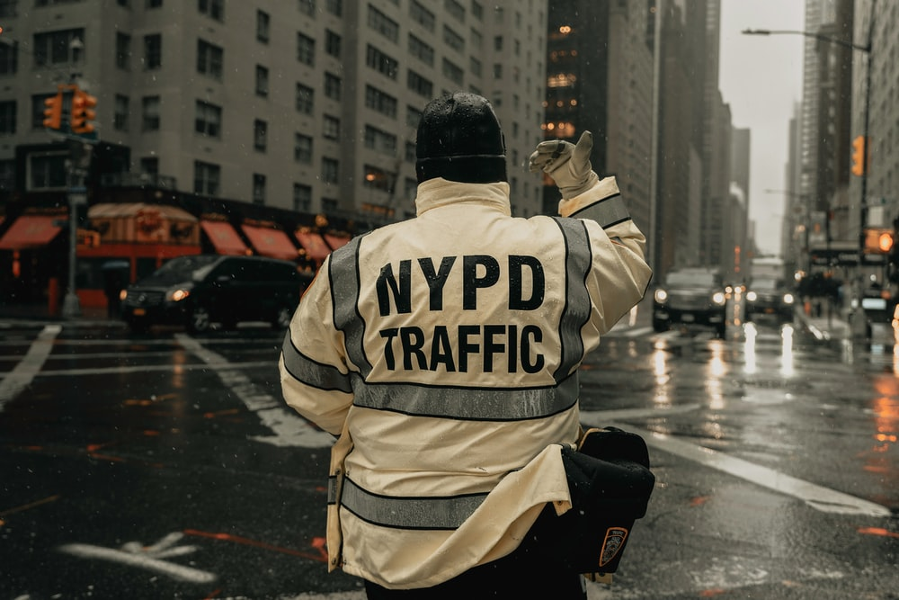 person wearing NYPD traffic in the middle of the road