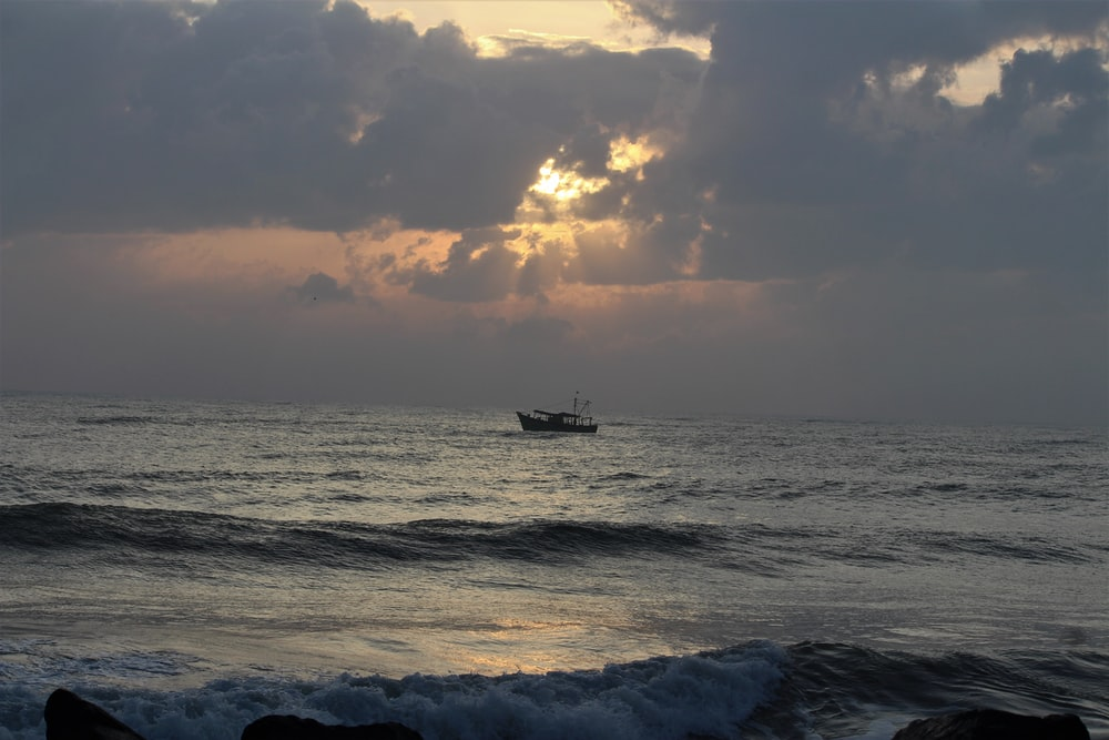 silhouette photography of boat on ocean during daytime