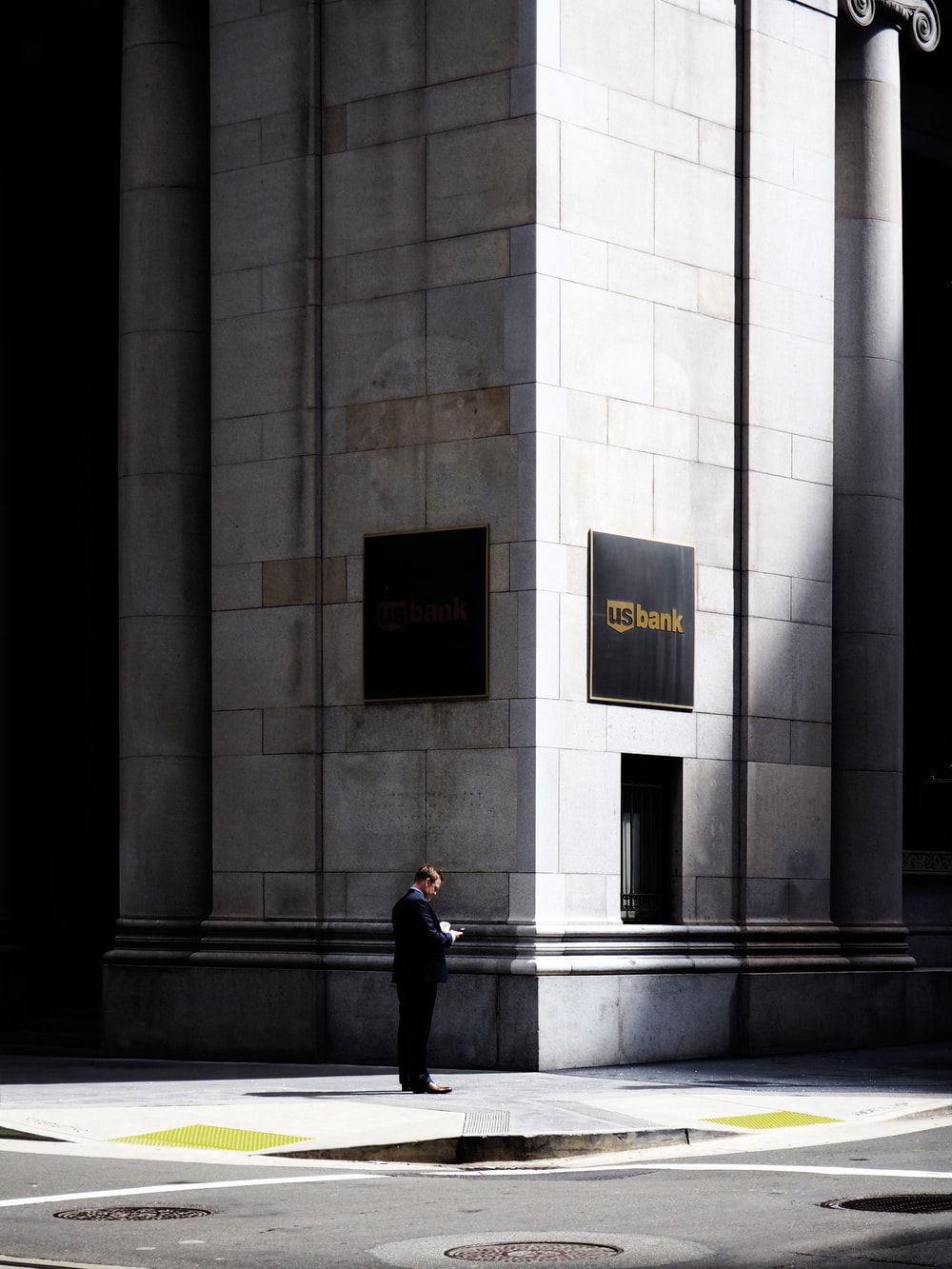man standing near road beside building during daytime