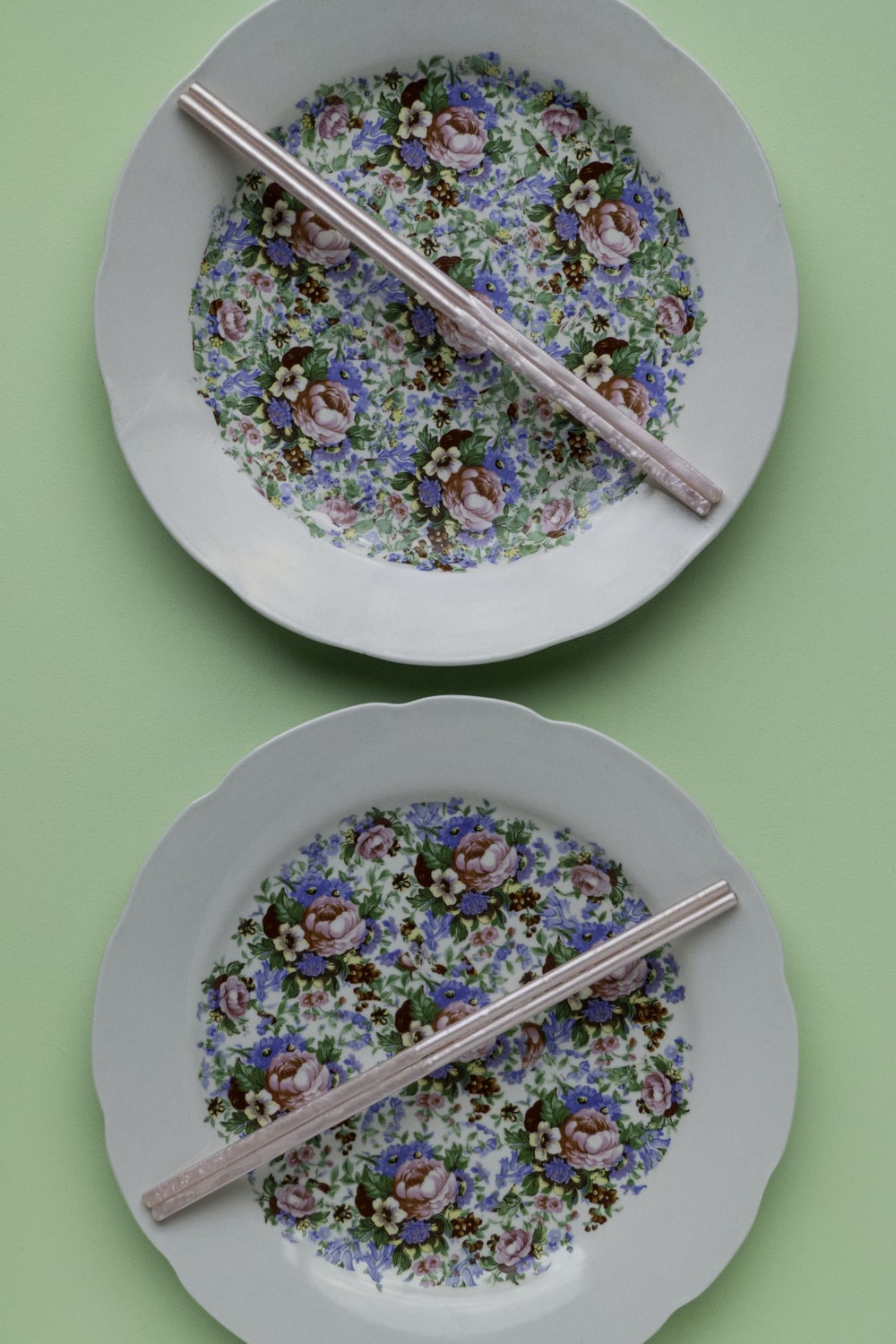 two round white-green-and-pink floral ceramic plates