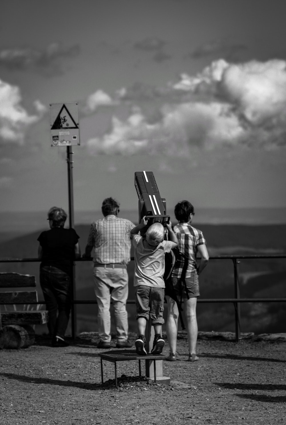 grayscale photography of four person standing while looking on mountain ranges