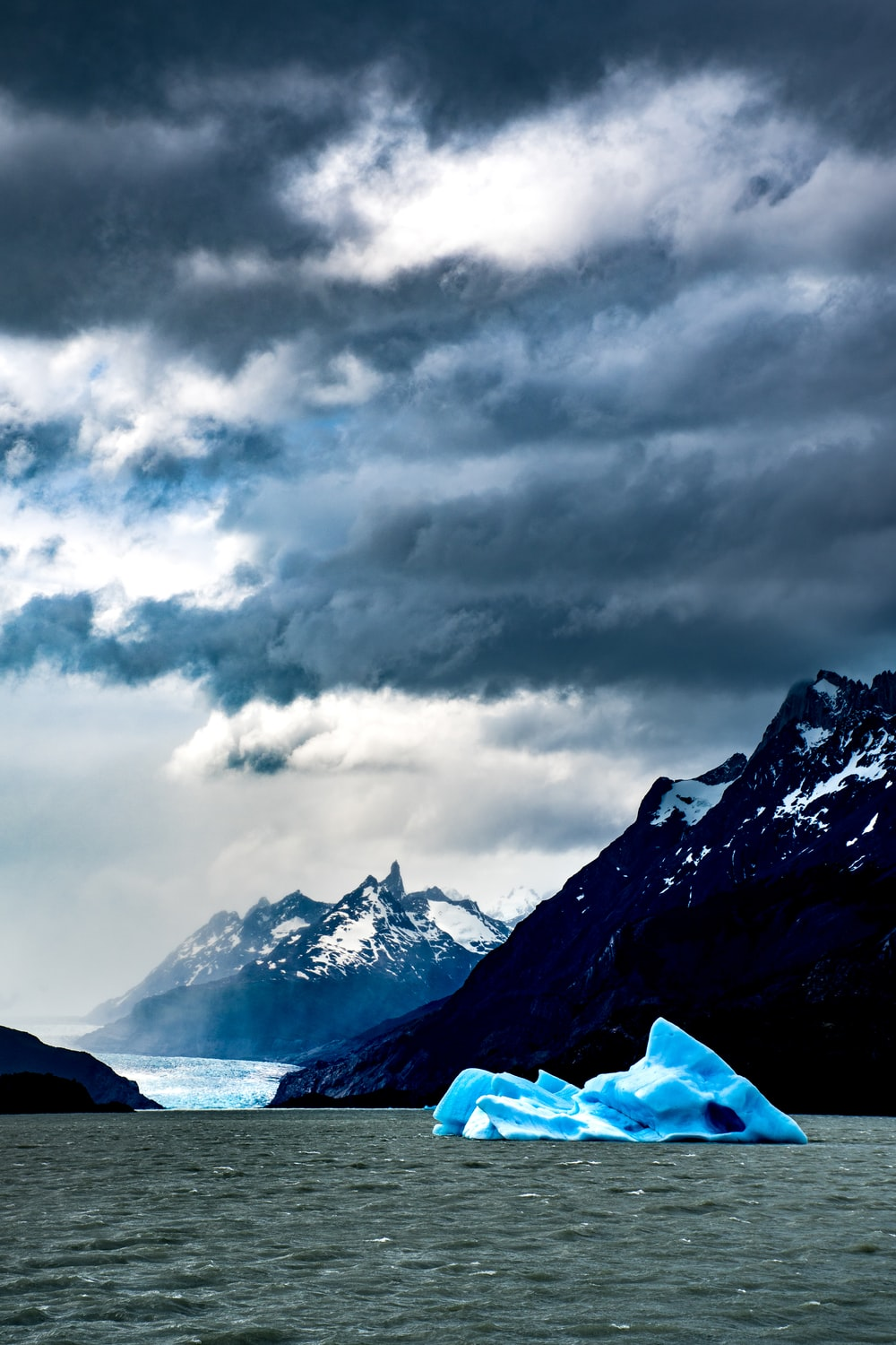 iceberg viewing mountain covered with snow under white and gray sky