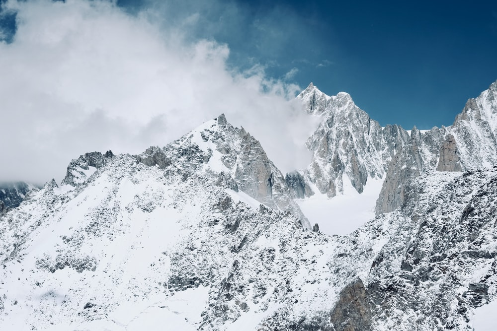 summit view of mountain covered with snow under white and blue sky