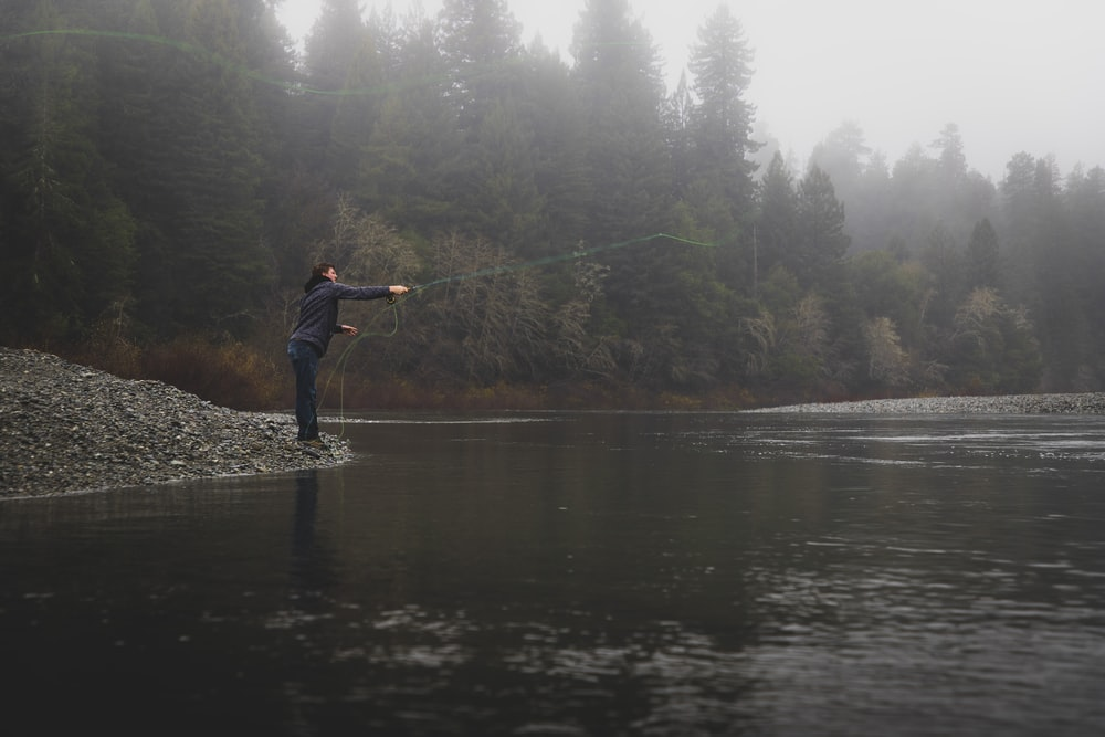person casting line on river during foggy weather