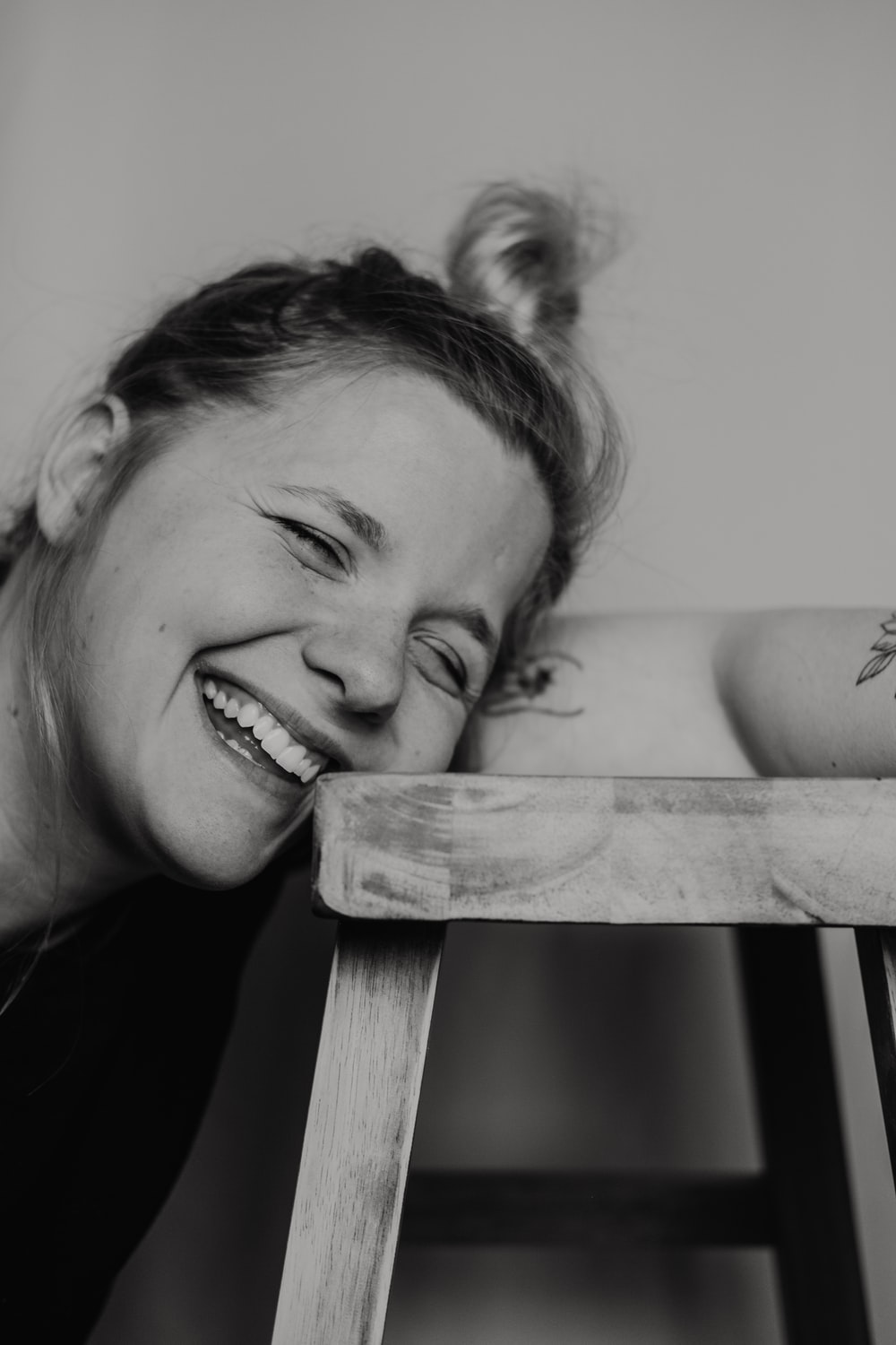 grayscale photo of woman smiling and leaning towards stool