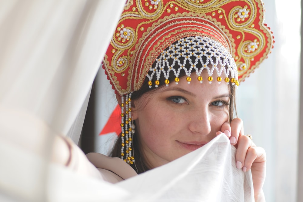 woman holding textile wearing headdress