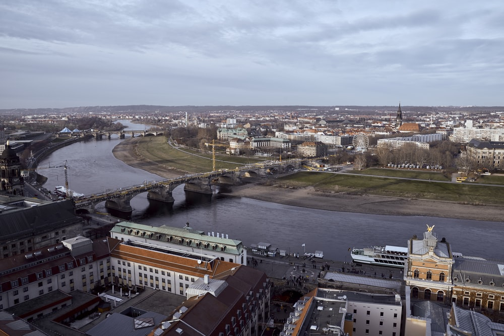 aerial photo of buildings near river with bridge