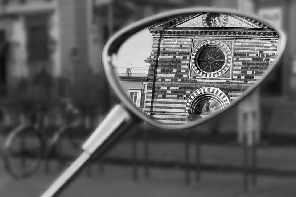 grayscale photography of historic building reflecting on side mirror