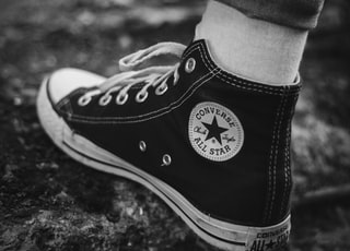 grayscale photography of person in Converse high-tops