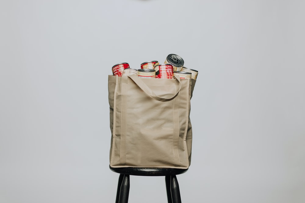 red labeled cans on white fabric handbag