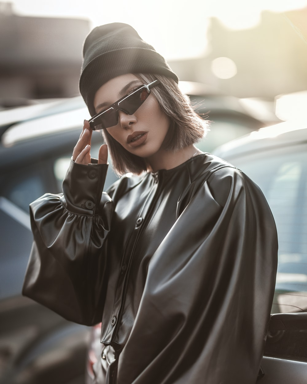 woman wearing black long-sleeved blouse and sunglasses standing near vehicle