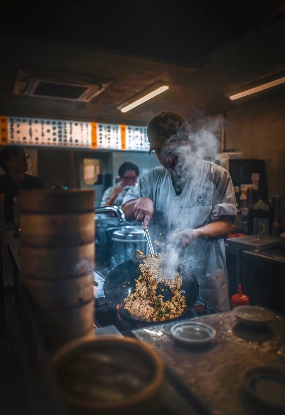 man standing while cooking food near people sitting