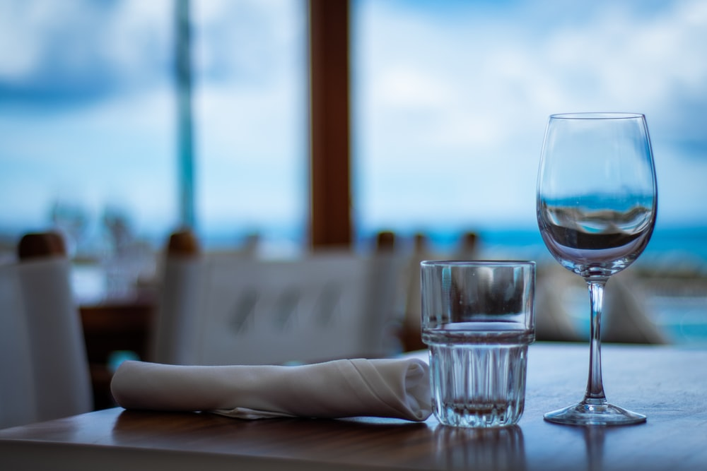 two empty wine and drinking glass near table napkin on wooden table