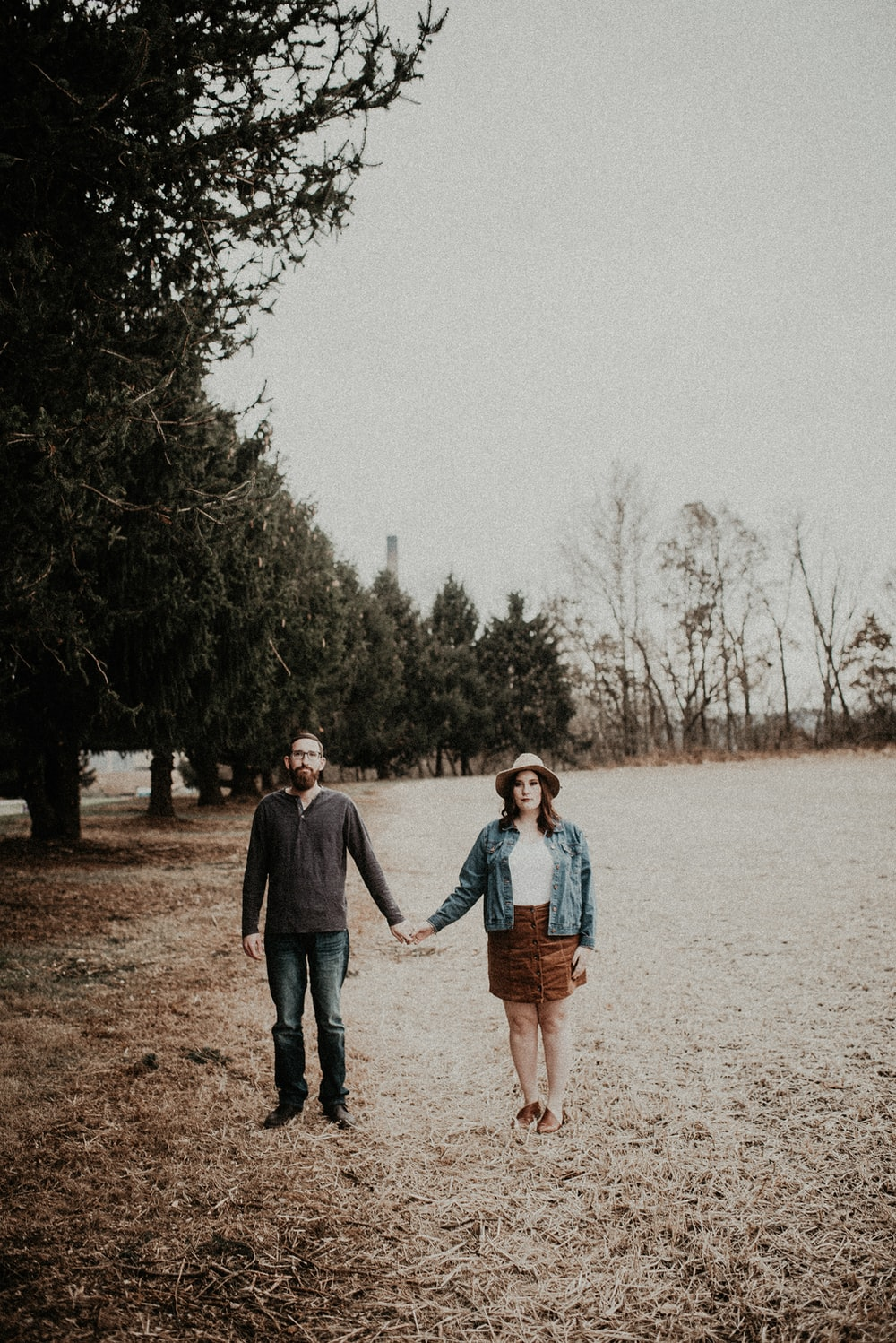 man and woman holding hands while standing on green field